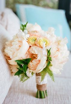 Peach peonies and ranunculus make this bouquet a spring bride's dream. Add bright greenery for a little extra color, like Out of the Garden, a South Carolina-based florist, did here.