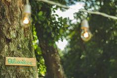 Plaquinha de madeira pintada à mão pendurada na árvore + varal de luzes