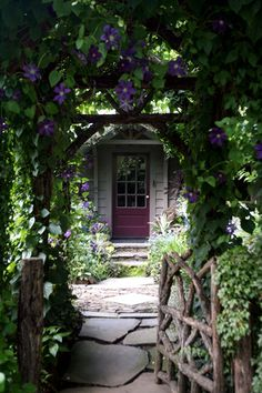 """When landscape designer David Ellis bought this Virginia-Highland home in 1997, the front yard was filled with dead shrubs, poison ivy and crab grass. ""There was nothing worth saving,"" said Ellis, of Ellis LanDesign. He added the rustic fence and uses topiary-like holly trees, foxgloves and flowering vines such as clematis and roses for a decidedly English touch."""