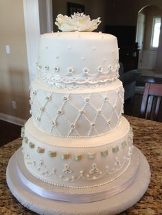 My son and new Daughter in law's wedding reception cake.  It was covered in fondant,  had a gum paste ribbon insertion, fondant eyelet lace and pearls, baby sugar paste blossoms,  royal icing accents as well as a large sugar paste blossom on top.