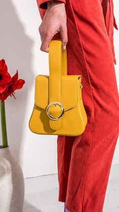 Raey bag in yellow. Top handle, front flap magnetic snap tab closure. Interior pockets. Detachable shoulder straps. Structured bottom. COMPOSITION AND CARE Dry Clean Only Synthetic Leather SIZE AND FI