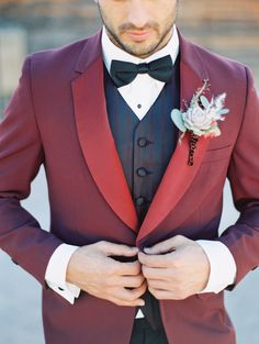 Whimsical but still classy - red tux jacket with subtly striped vest for the groom. Amazing boutonniere!