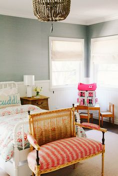 Children's bedroom with colorful patterned bedding, white bed frame, wood bedside table, white lamp, light pink rug, and dollhouse