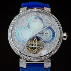 This Louis Vuitton Tambour watch features a carved mother-of-pearl flower with a tourbillon housed in one of its four petals. Discover what a tourbillon watch is in our in depth and fashionable guide to watches for men and women: http://www.thejewelleryeditor.com/watches/what-is-a-tourbillon-watch/ #style