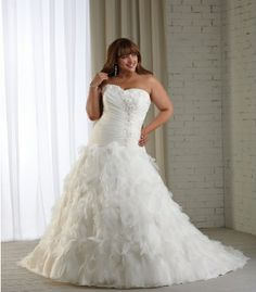 This plus size strapless wedding gown is perfect for a summer wedding.