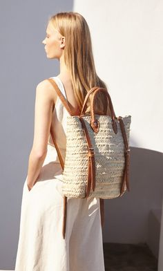 MARKEY RUCKSACK. Utilitarian woven straw bag with sturdy leather back straps and rolled leather handles.