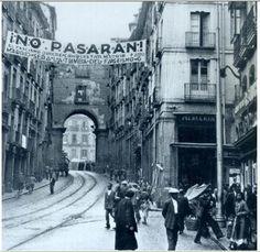 Calle Toledo durante la Guerra Civil (Madrid, 193X)    Foto de Madrid durante la Guerra Civil Española. En ella se puede ver la pancarta más popular de la guerra en la que se lee:    ¡NO PASARÁN.!  El fascismo quiere conquistar Madrid.  Madrid será la tumba del fascismo.