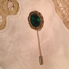 "Vintage Gold-Tone Emerald Rhinestone Stickpin The ornately framed large Emerald rhinestone on this gold-tone stickpin is encircled in a leaf crown.  Approx. 3"" tall. Top is 1"" x 3/4"". This stunning piece is in excellent  preowned vintage condition. Looks wonderful on a vintage hat or on your lapel. Would make a great gift or addition to one's own vintage jewelry collection! Vintage Jewelry Brooches"