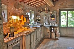 Stone-walled farmhouse kitchen with rustic wood cabinetry.