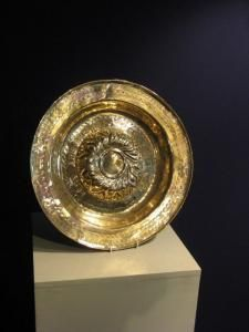 A LATE 16TH CENTURY NUREMBERG BRASS ALMS DISH.-WITH A RAISED CENTRE WITH REPOUSSE GADROONED FOLIATE MOTIFS, SURROUNDED BY A BAND OF TEXT.