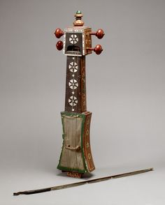 Sarangi, 19th century, Gujarat, India,62.8cm. A sarangi is a bowed stringed instrument with a skin-covered resonator. The typical sarangi is made by hand, usually from a single block of tun wood. The playing strings are usually made of goat gut, but on this example the top two strings are metal. This small sarangi is unusual in that it does not have sympathetic strings.