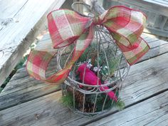 Handcrafted one of kind Christmas decoration.  Small white bird cage filled with various greenery and pinecones.  A red bird sits on top of the greens.  A big plaid bow is tied at top of cage.  $50