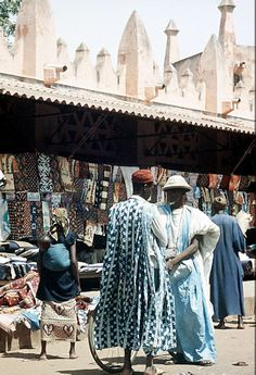 Africa | Two men talking at the clothes selling section of the market.  Bamako, Mali.  1959 | ©Eliot Elisofon