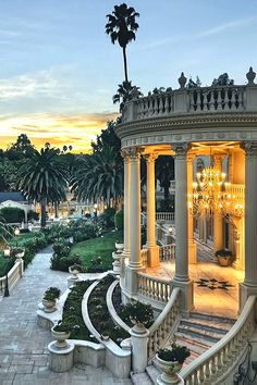 Outdoor terrace w/ columns, a chandelier, and palm trees.