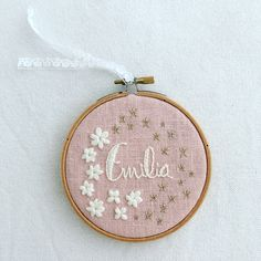 Pink linen and white and gold floss, embroidery name.