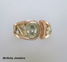 To say this ring is stunning in an understatement! We worked closely with our client to create a ring that would highlight the gorgeous center diamond. The N color of the diamond is enhanced with an 18kt yellow gold bezel and wire accents, all set in a rich 18kt rose gold setting. A stunning work of wearable art! McNulty Jewelers original design