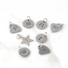 Gorgeous add on charms for DOSE of ROSE jewelleryYou can choose from 3 different types of personalised charms to create your own jewellery. They are all hand stamped so all the intials and numbers will be individual style and look a little bit different to each other. A great little touch to personalise your own jewellery or make a little special gift for someone you love with these cute add on charms for DOSE of ROSE jewellery.Brass star in rhodium plated and stainless steel circle/heart…
