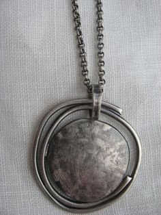 This necklace consists of a forged piece of sterling silver enclosed in a swirl of thick stock silver wire. It measures approximately 1 1/2