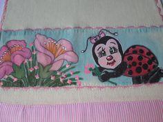 Detalhe da fralda de boca amarela, com pintura em toda a faixa, motivo joaninha entre flores.