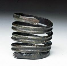 "Viking Bronze Serpentine Hair Ring  Northern Europe, Ca 10th to 13th century. Rare Viking bronze hair ring, comprised of continuous flat coiled bronze, head of a snake on each end and entire length decorated with added incising. 1-3/4"" H by 1-1/2"" D."