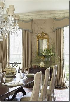 Ornate curtain Pelmets with dramatic drapes, wallpaper, crown moulding, long table for 8 with upholstered chairs, chandelier.