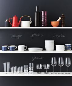 cute kitchen organizing idea: Dishes stacked on shelves in front of chalkboard wall
