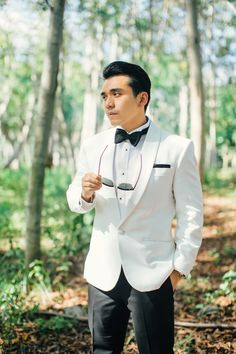 Groom looking dapper in a white suit and black bowtie // Luxurious Wedding at AYANA Bali with the Bride in Krikor Jabotian
