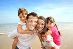 Stock photo of Parents giving piggyback ride to kids at the beach 54468439 - image 54468439