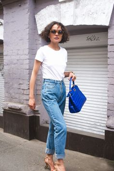 25 Ways to Make Mom Jeans Look Modern - minimal + classic style: white t-shirt, high-waisted mom jeans, bright blue handbag, + nude leather heels. Oh, and her wavy bob—tousled perfection | StyleCaster