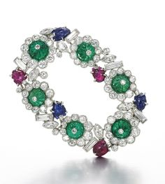 GEM SET AND DIAMOND BROOCH, CIRCA 1920 Of garland design, set with carved emeralds, rubies and sapphires and circular-cut, baguette and marquise-shaped diamonds, French assay and maker's marks for Henri Picq.