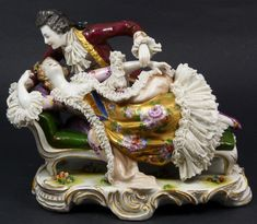 Antique Dresden French porcelain group figure depicting a courting couple. The woman is depicted laying on a day bed and the man leaning over her from behind.