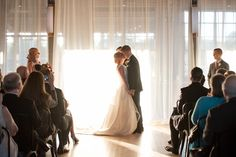 Mikkel Paige Photography photo of a wedding at The Rickhouse, Durham. A picture of the bride and groom's first kiss during their indoor ceremony.
