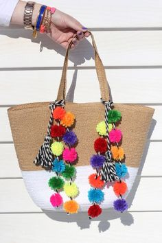 Accessorize your tote or beach bag using this easy DIY pom pom tutorial.
