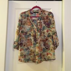 Floral top Pretty watercolor floral top with 3/4 elastic sleeves. Flattering v neck with buttons. Worn, but in excellent condition. Size is a petite large. a.n.a Tops Blouses