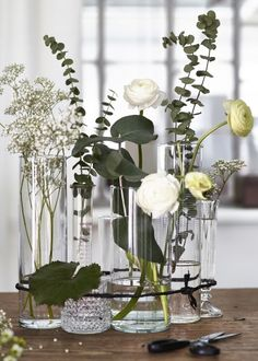 Clear vases and glasses bound together with twine make an unconventional display - a unique and modern take on the traditional floral arrangement.