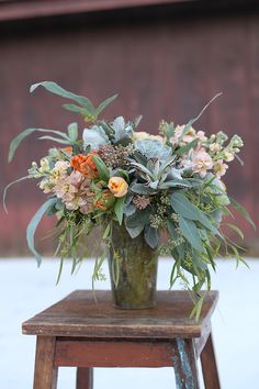 Peach and blue centerpiece in a patinaed copper pot by Cincinnati wedding florist Floral Verde LLC.  Centerpiece contains orange tulips, Chablis spray roses, peach stock, seeded eucalyptus, willow eucalyptus, blue star fern, Kalanchoe tomentosa, Echeveria lilacina and dusty miller.