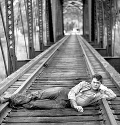 Tony Curtis waits for the locomotive on railroad tracks during the making of the movie Anna Karenina.