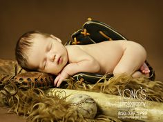 Tallahassee baby and family photographer, Linda Long of Long's Photography, creates a favorite for parents who love and still play baseball!  This adorable newborn baby boy is found tucked into his dad's glove with ball and bat, ready for action!