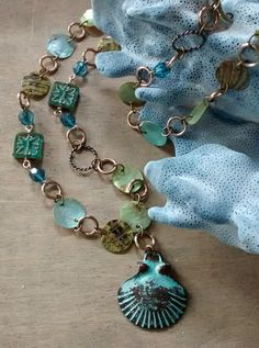 Handmade light green and turquoise blue cut shell, silver metal chain linked necklace, with a turquoise blue patina metal Scallop shell pendant. Materials: Mixed Metal, Patina Metal Shell, Capiz Shell