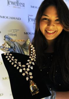 "Jessica Nasr, a staff member of Dubai-based jewellery firm Mouawad, holds the 637-carat ""L'incomparable"" necklace."