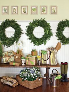 Entryway with white white, beadboard wainscoting, three boxwood wreaths, and a vintage bench covered with Christmas gifts