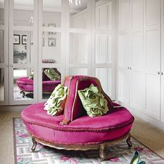 Mirrored wardrobes make the most of space in this dressing room, and also bring light into the room. The pink rounded chair is a striking focal point which, when styled with decorative cushions in a contrasting colour, give the room a Hollywood feel.