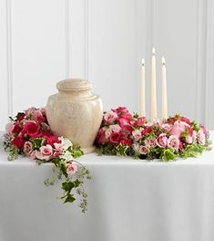 Candle Urn And Flowers Arrangement at Send Flowers. A funeral flower design that goes around the urn at a gathering with pink and spray roses and candles. Arrangements Funéraires, Funeral Floral Arrangements, Funeral Sprays, Funeral Urns, Memorial Flowers, Funeral Memorial, Funeral Planning, Sympathy Flowers, Funeral Flowers