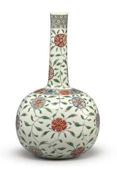 A FAMILLE-VERTE BOTTLE VASE, QING DYNASTY, KANGXI PERIOD. Of globular form rising to a tall cylindrical neck and lipped rim, with stylized floral medallions borne on leafy scrolls, the shoulder with alternating flower heads on an aubergine stippled ground, the neck with further stylized floral meander and surmounted by a diaper cell band, the base with an underglaze blue 'G' mark.