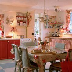 Cozinha romântica com estampas florais, na cortina da janela, na cortina da pia, até nos aventais e panos de copa