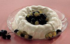 Is med marinerede vindruer Hjemmelavet vaniljeflødeis med blå og grønne druer i en marinade af hvid rom som tilbehør.