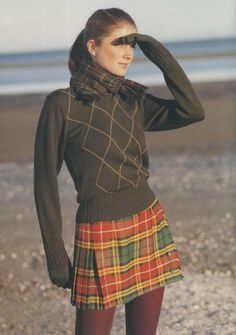 Young Woman on a Beach Shielding Her Eyes as Cairistìona Looks into the Sun as She Is Wearing a Imperial Red, India Green, Primary Yellow, & Deep Peach Mini Kilt w. a Pale Brown Diamond Design on Front of Her Sweater, Taupe Scarf & Crimson Leggings. Tartan Fashion, Look Fashion, Fashion Outfits, Fashion Trends, Stylish Outfits, Fall Outfits, Cute Outfits, Mode Tartan, Tartan Plaid