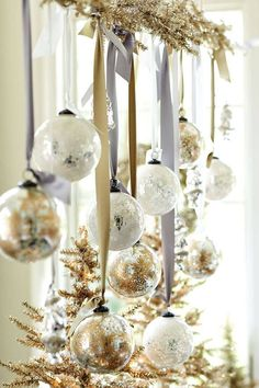 Hang ornaments from metallic ribbons and garland for a festive flair.    - HarpersBAZAAR.com