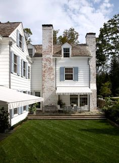white washed brick, cedar shake roof, blue stone patio, striped awnings.