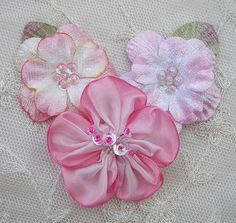 Thank you for stopping by my store today.    Up for your consideration is ONE Floral Applique in colors of Pink, White and Cream. This applique is a grouping of 3 flowers. 2 of the flowers are velvet with green velvet leaves off to the side. The 2 velvet flowers are filled in the center with tiny cupped sequins tipped with glass seed beads and the1 larger flower at the bottom is fashioned with ombre wired ribbon with a cluster of glass seed beads tipped with tiny sequins. The color…